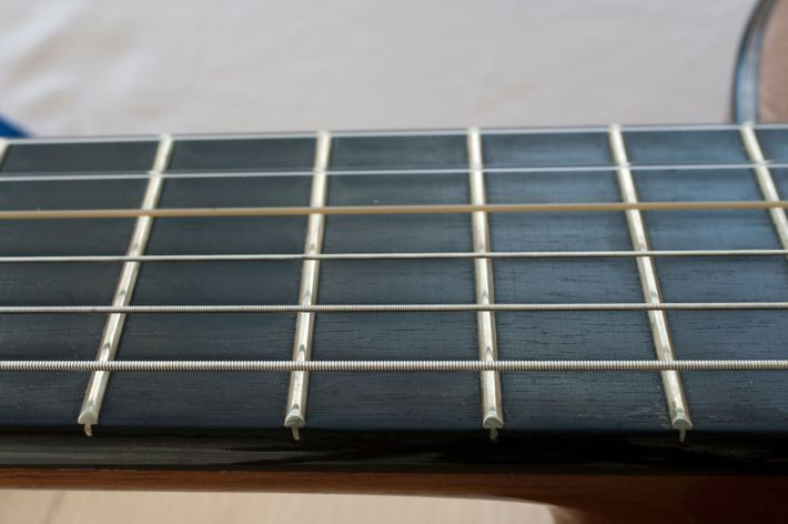 An ebony fretboard on an acoustic guitar. Other woods such as rosewood and maple are also ...