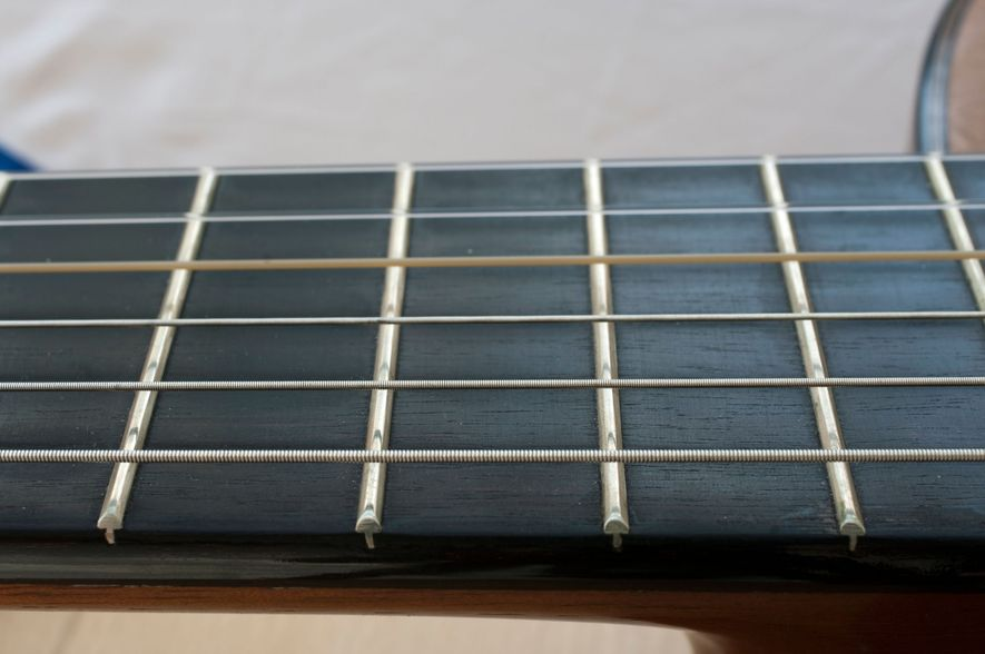 An ebony fretboard on an acoustic guitar. Other woods such as rosewood and maple are also used, but ebony's durability and tone has made it a popular choice for instruments.
