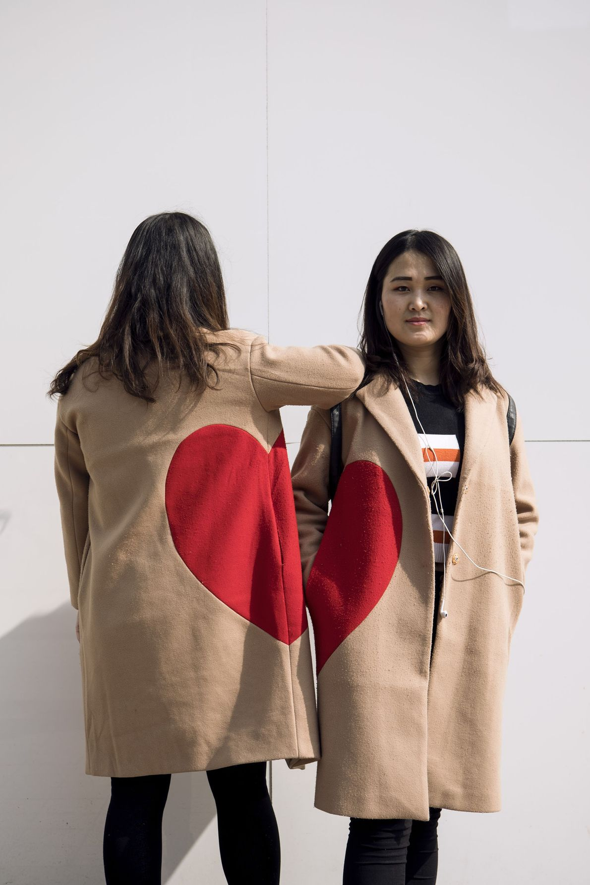 Two girls wear matching coats with a heart design