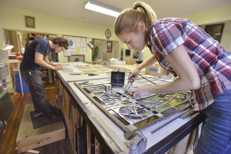 Apprentice Adam Choquette (left) and stained glass artist Cecile Coisne in the workshop of Jim Anderson Stained Glass in Boston's South End neighborhood. Image: Josh Reynolds