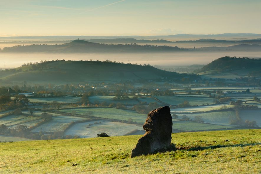 An ancient standing stone on the Mendip Hills overlooking Glastonbury and its Tor.