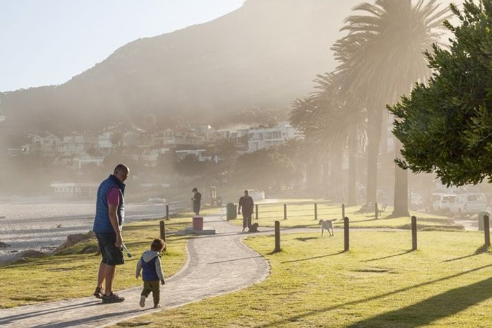 Sunrise strolls on Camps Bay promenade.