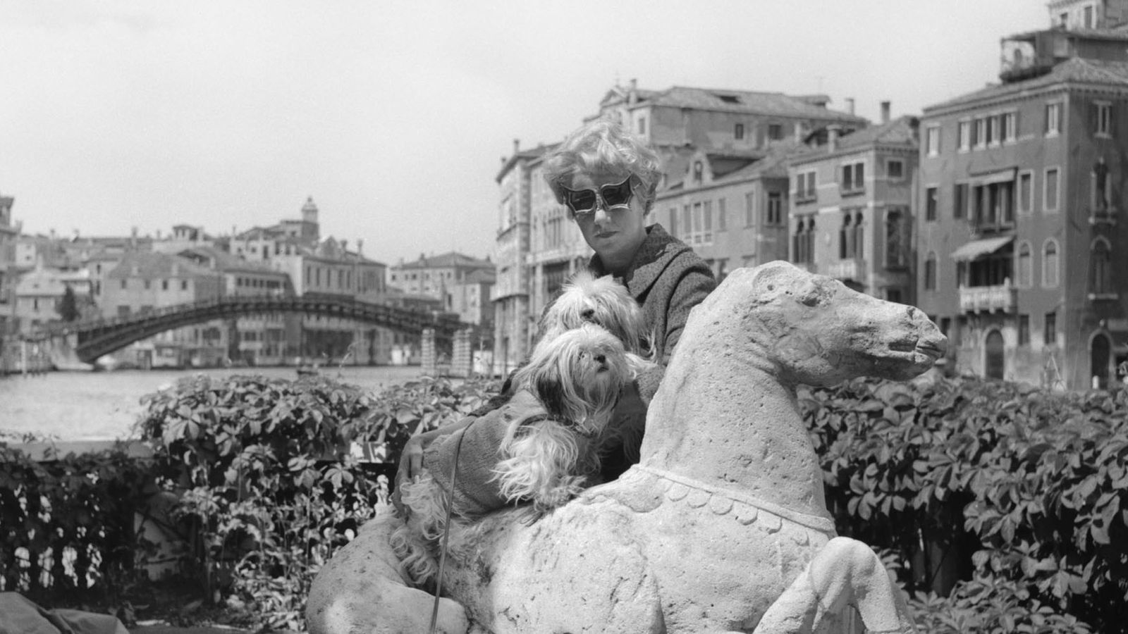 Peggy Guggenheim with her Lhasa Apsos terriers on the terrace of Palazzo Venier dei Leoni.