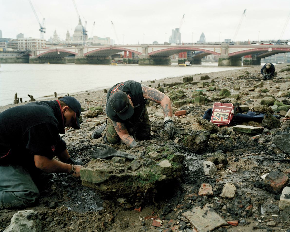 Southwark, London: 'Mudlarking,' or foraging for items of interest, on the banks of the Thames at ...