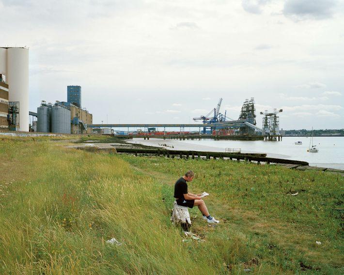 Grays, Essex: a man reads the Sunday paper in a quiet spot near Tilbury docks.