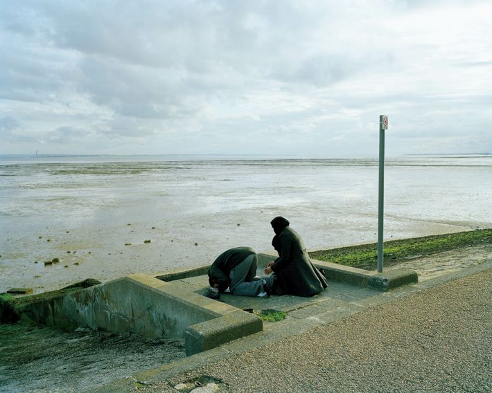 Southend-on-Sea, Essex: Day trippers from East London perform Islamic evening prayer, Maghrib, at the edge of the Thames ...