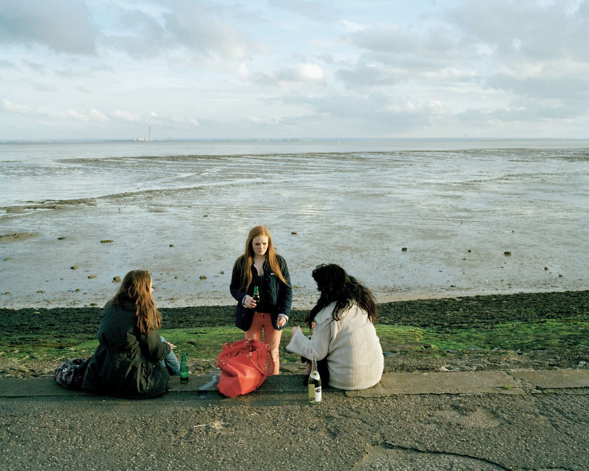 Southend-on-Sea, Essex: girls drink by the water near the Southend amusements.