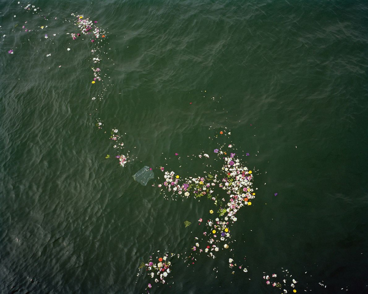 Southend-on-Sea, Essex: floral tributes drift on the water at a place where ashes were scattered. The ...