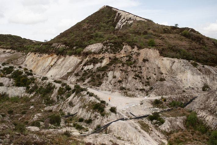 A worker walks beneath one of many industrial-spoil mountains – known locally as the Cornish Alps ...