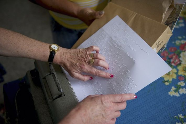 Mary reading braille at the School for the Blind. Image: Mark Stratton