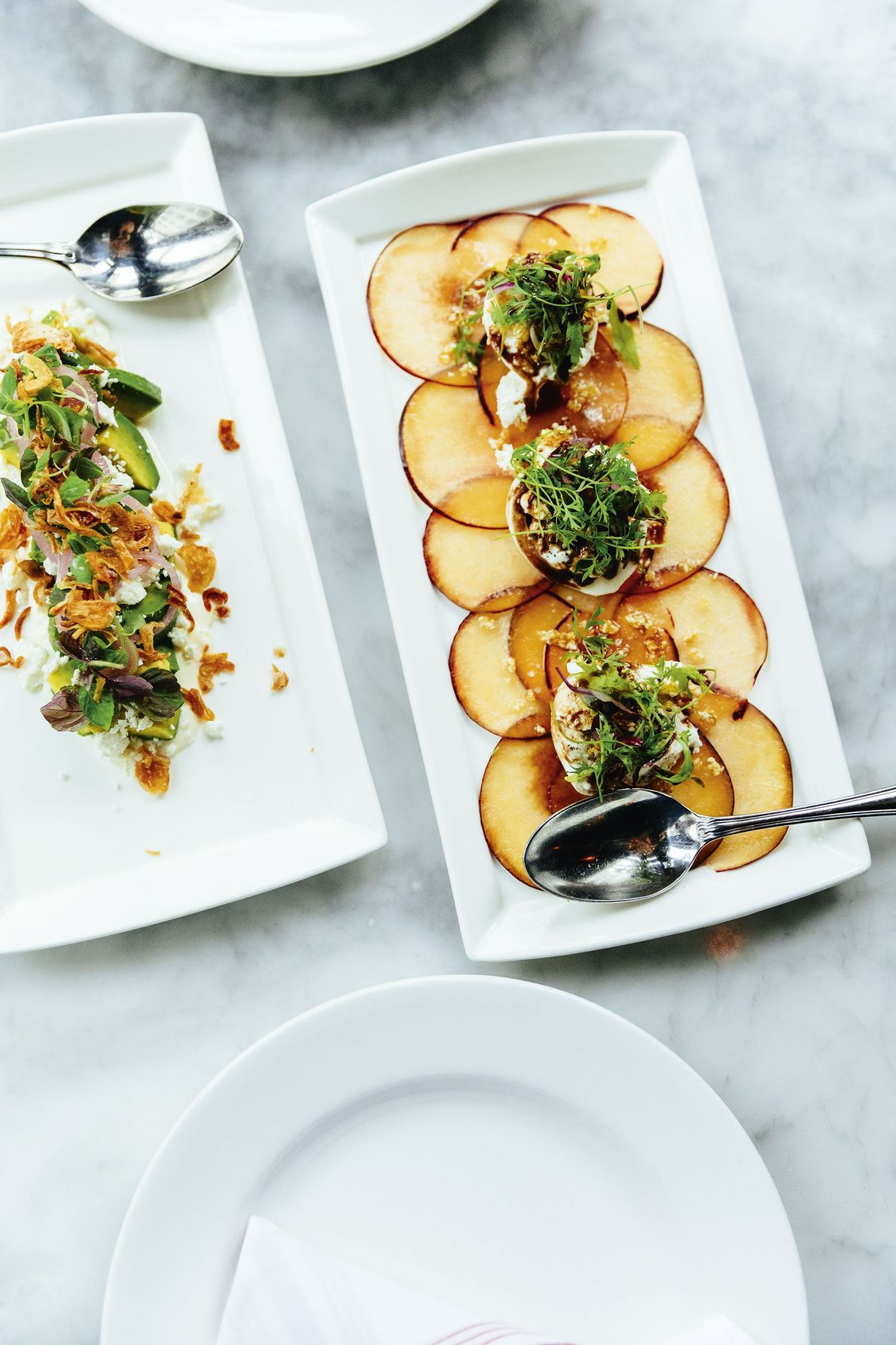 Avocado salad with feta and crispy shallots next to a burrata cheese plate with stone fruit, ...