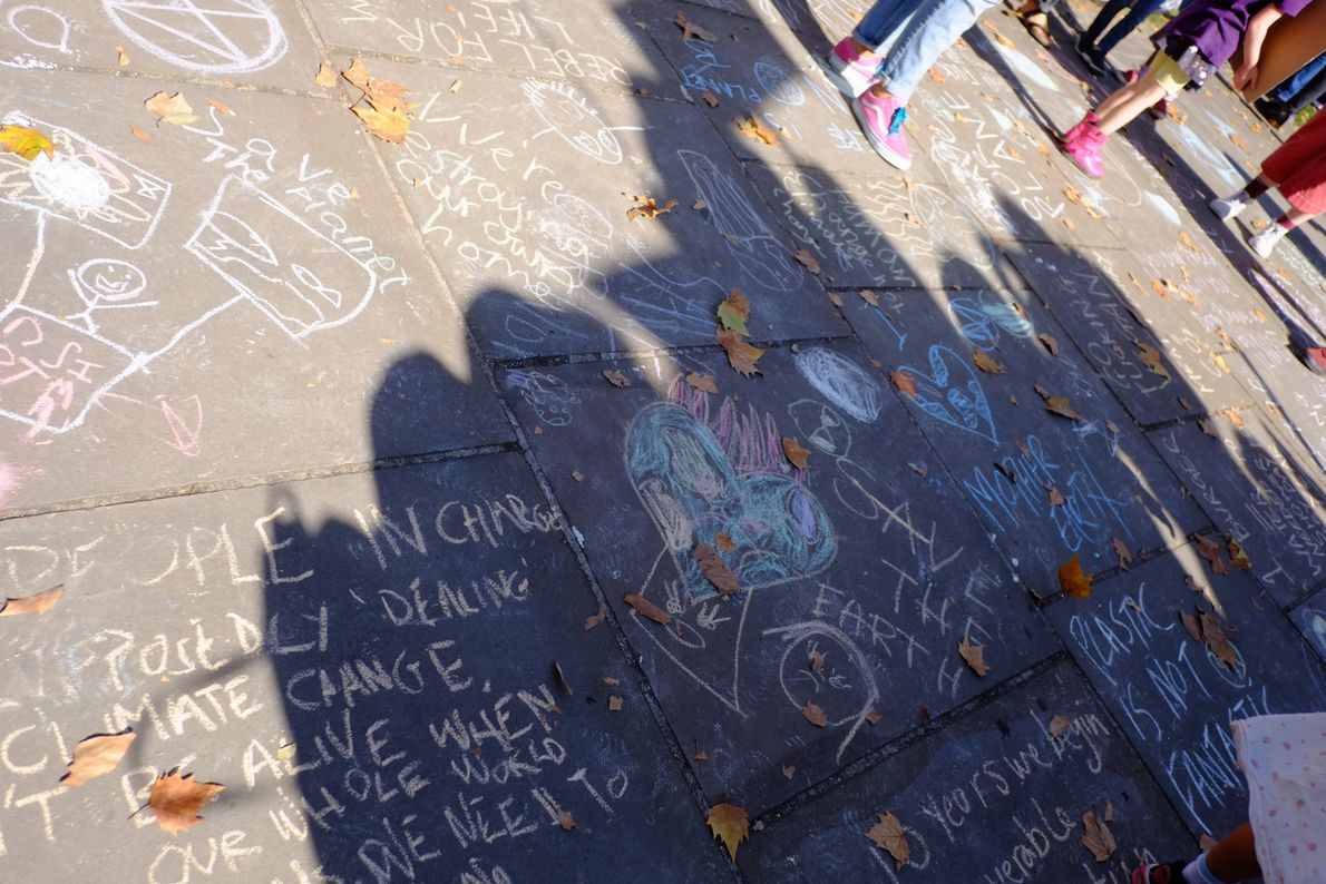 Chalk slogans on the floor in chalk beneath Rodin's the Burghers of Calais.