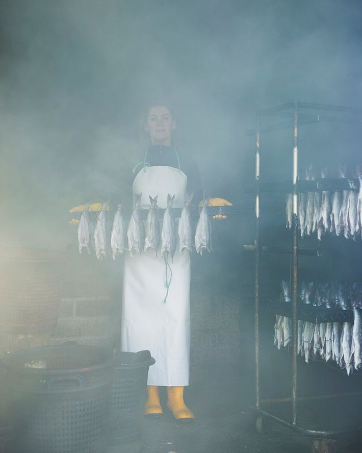 Margaret Smith with a rack of smoked haddock – to be made into the 'Arbroath smokies' – Arbroath, Scotland.