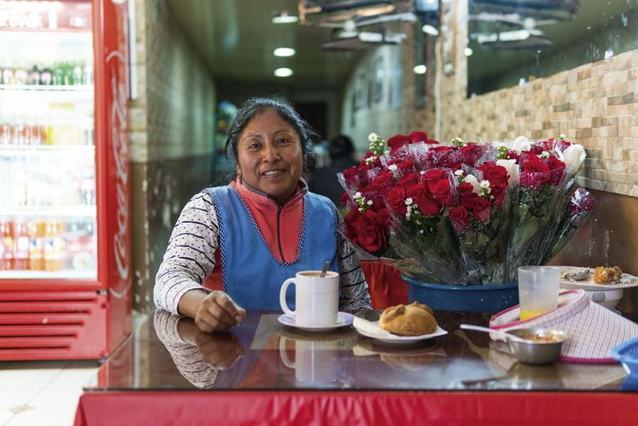 A flower seller enjoying hot chocolate with cheese