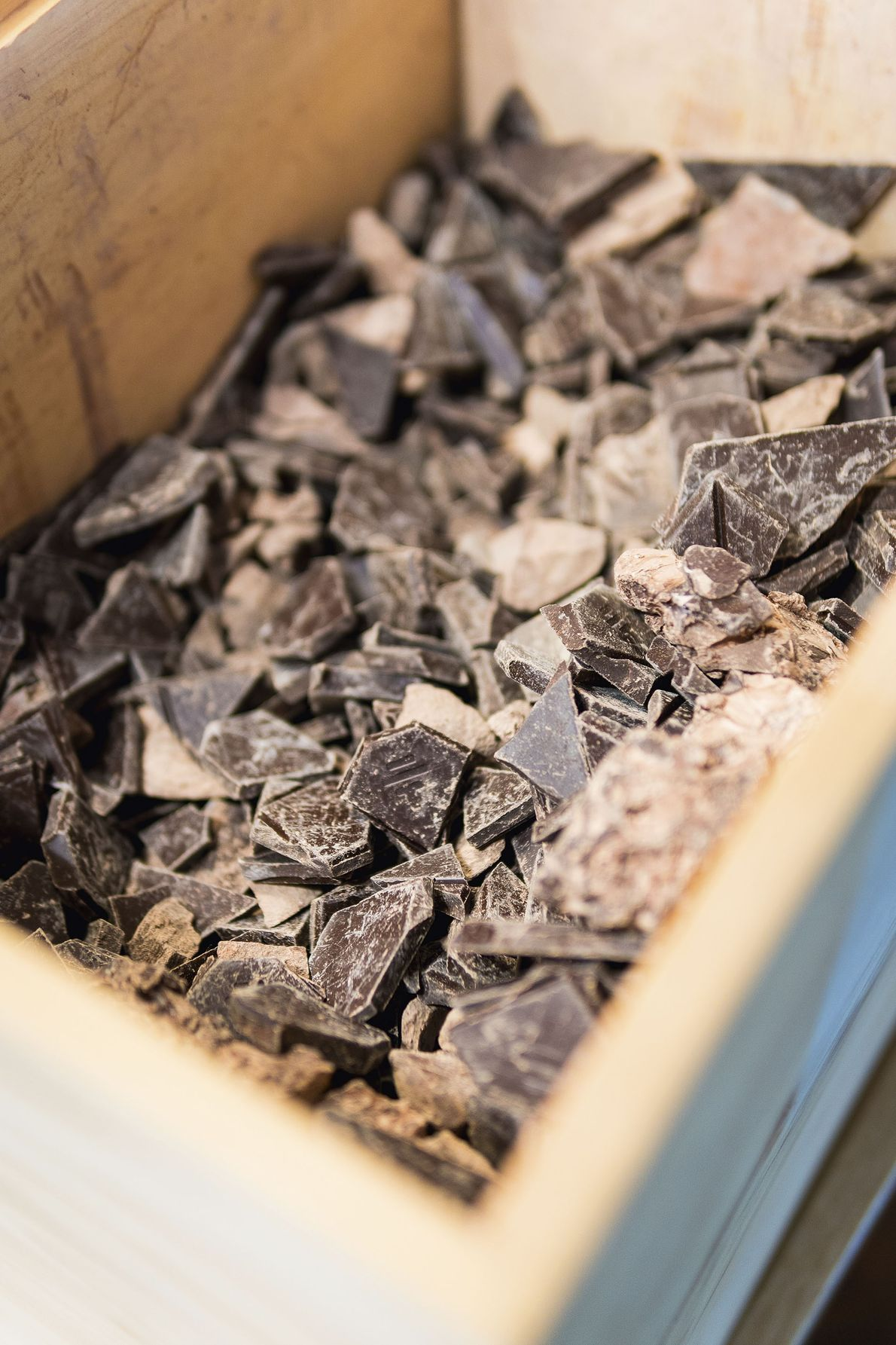 Chunks of To'ak chocolate being aged inside a wooden box.