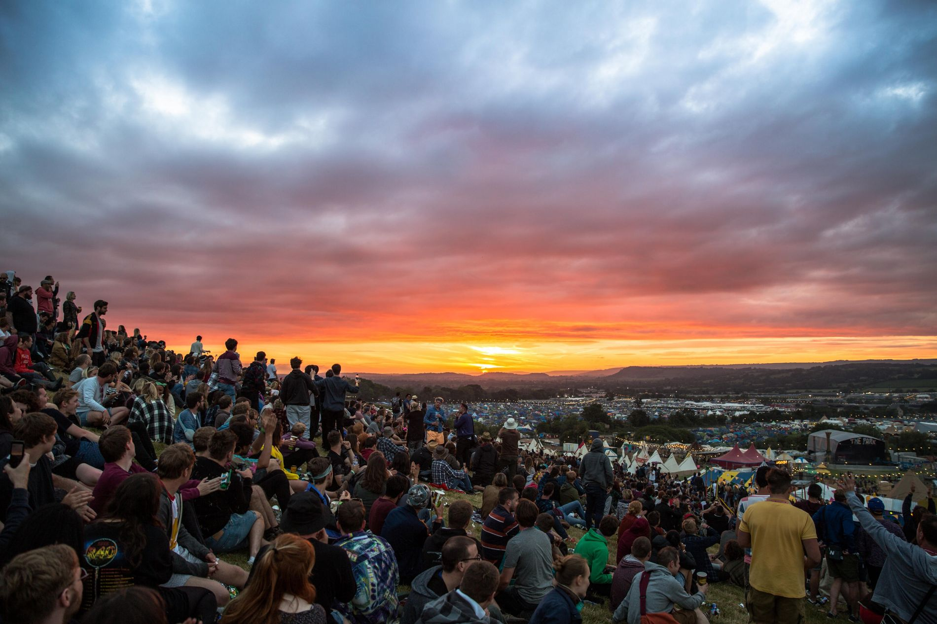 Festival-goers watch the sunset from Worthy Farm during the Glastonbury Festival.