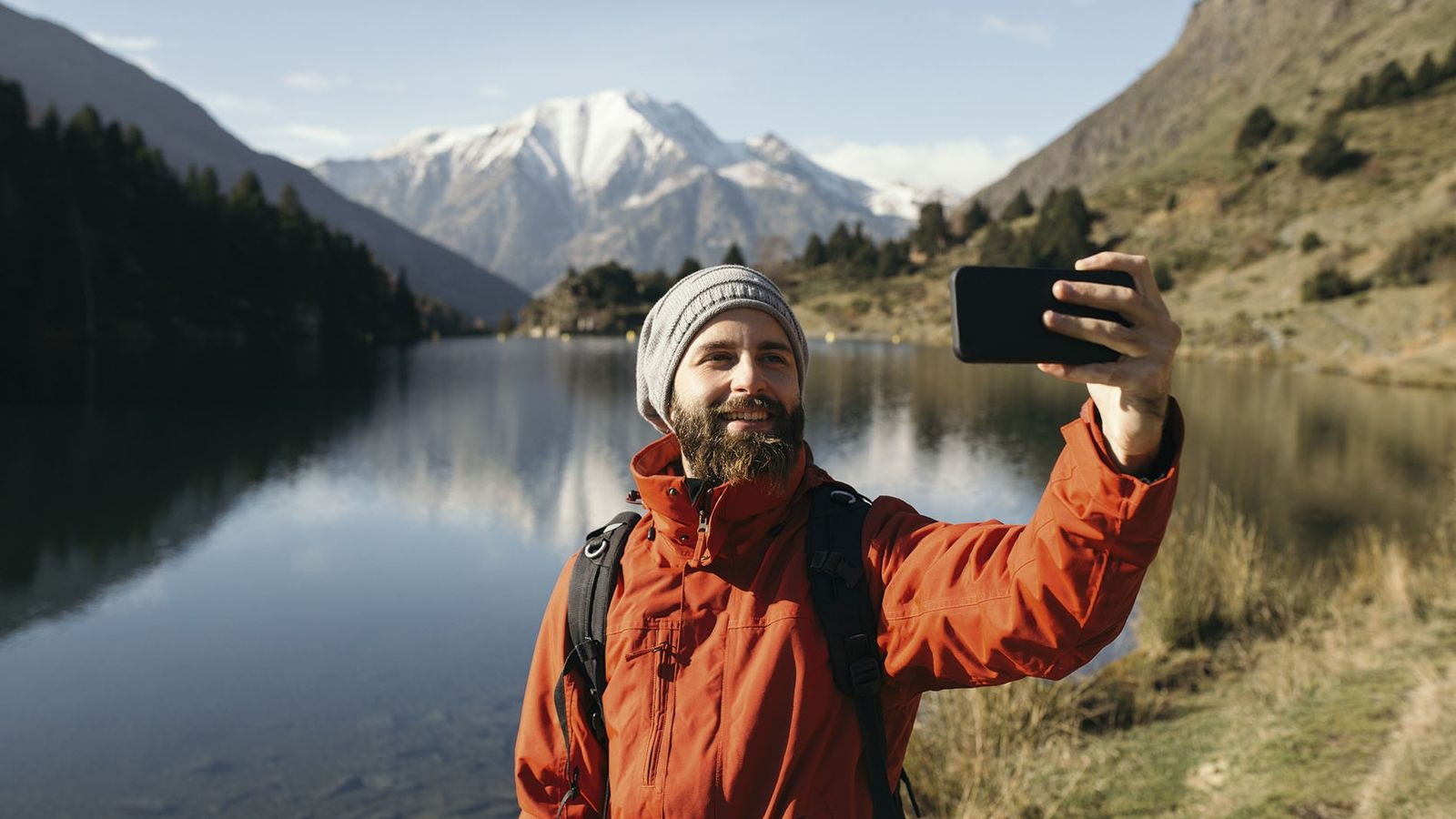 Man taking a selfie in front of a lake