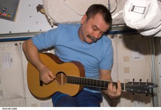 Russian cosmonaut Mikhail Tyurin plays a guitar in the International Space Station.