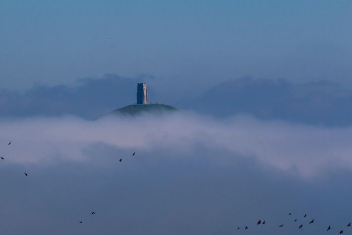 Glastonbury Tor rises above mist. The tor was once an island, and many 'Avalonians' believe it ...