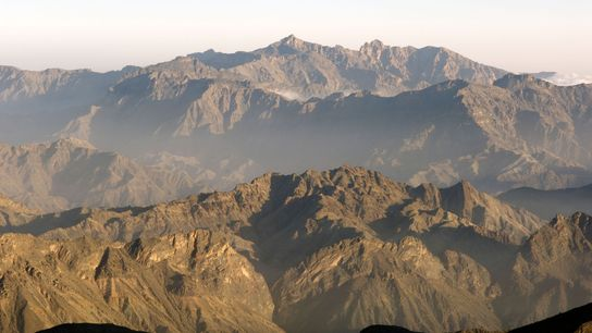 The peaks of the Hajar Mountains' western range stretch off into a sand-coloured sky.