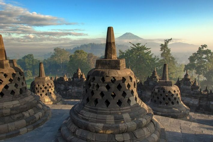 Borobudur temple complex, with the Mount Merapi volcano in the background.