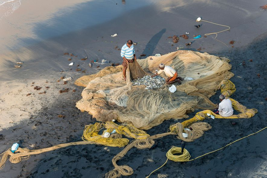 Fishermen inspect their nets in Varkala, Kerala.