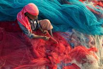 A fisherman in Kerala, India, repairs nets on a beach. Plastic pollution can damage and clog ...