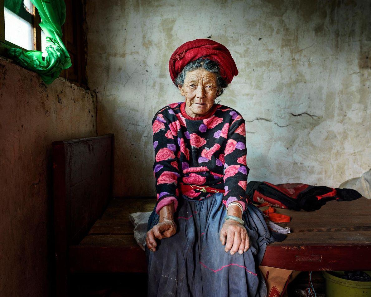 Pema Lamu, 73, sits in her bedroom in the village of Zhashi. Like many Dabu, her ...