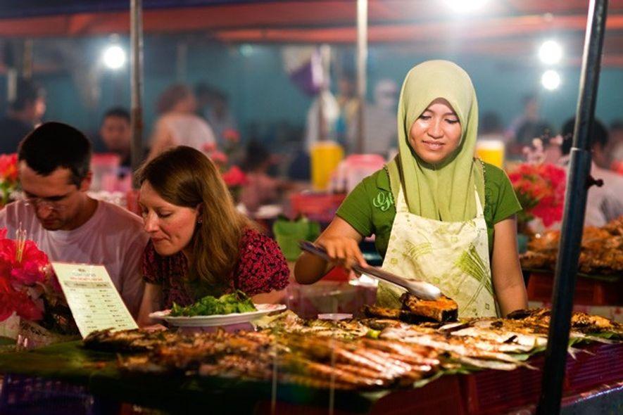 Woman serving food at a pasar malam or night market