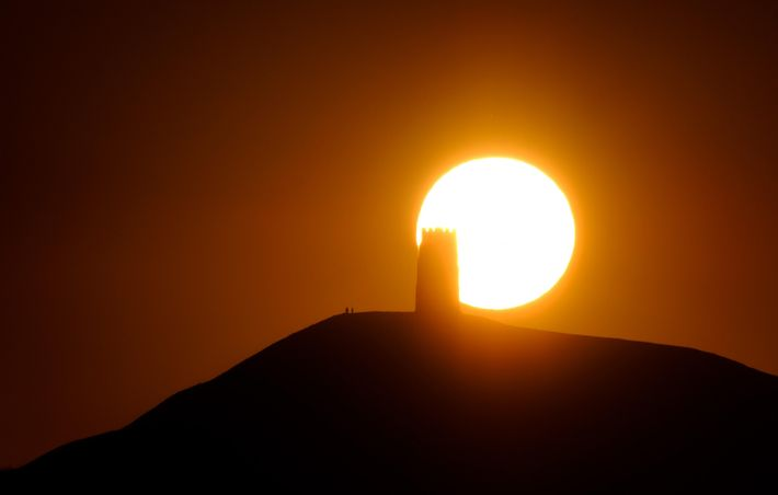 A telephoto lens captures the sunset over St Michael's Tower, Glastonbury Tor.