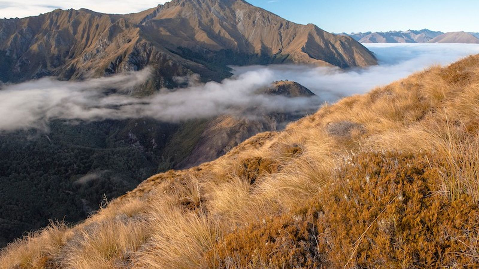 The morning sun hits the rugged landscapes near Mount Crichton above cloud-covered Lake Wakatipu near Queenstown, ...