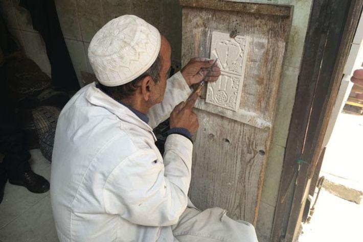 Artisan carving a Hamsa Hand motif into a tile.