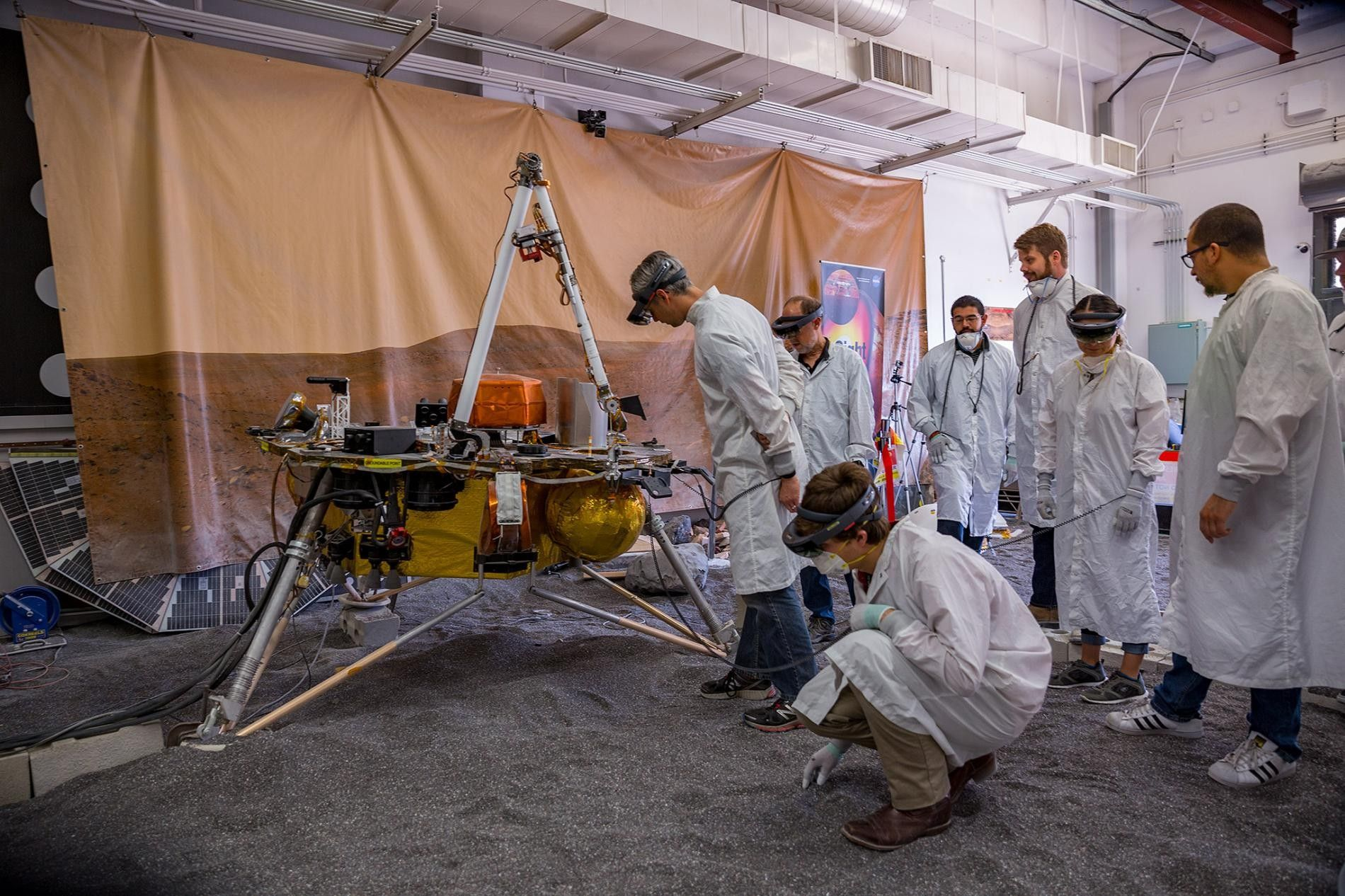 A team of scientists works with a replica of the InSight lander in the In Situ ...