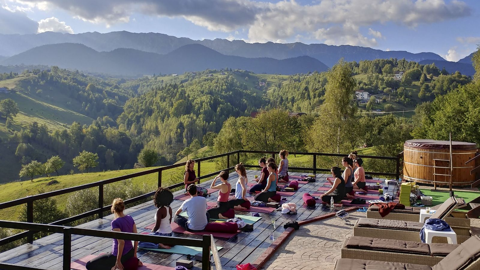 People practicing yoga outside on a terrace overlooking the mountains at Akasha Wellness Retreat