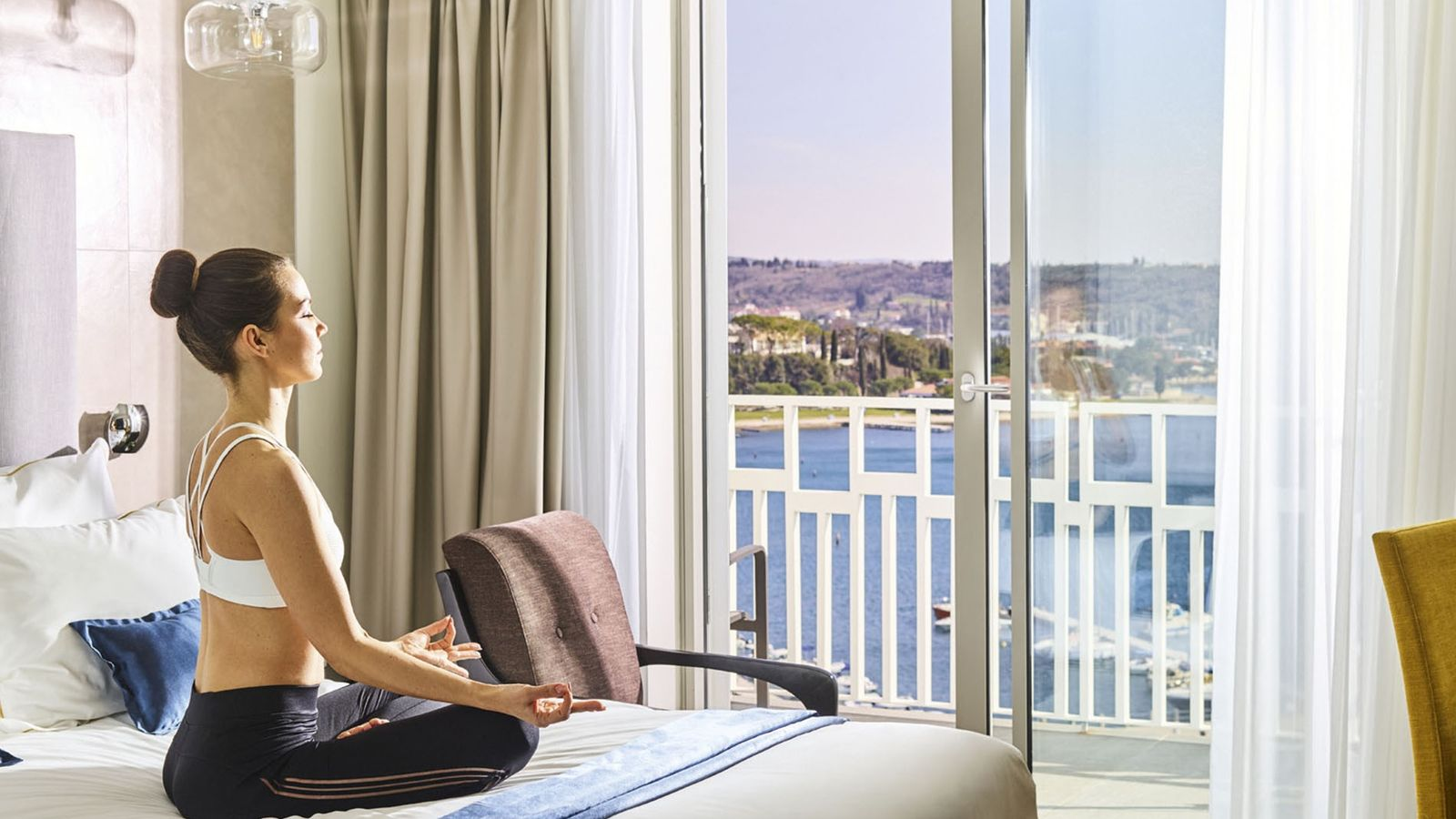 A woman meditating on the bed in her room overlooking the sea