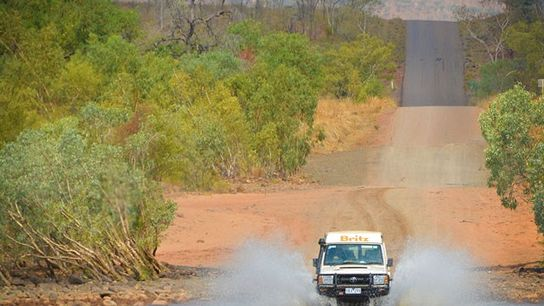 Car driving down the Gibb River Road in Western Australia