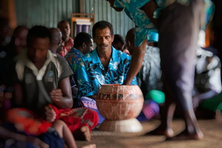 People sit cross-legged at a kava ceremony in Fiji