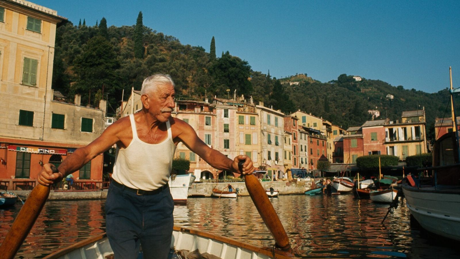 A man rows his boat into the harbour at Portofino, north-west Italy. Italians have some of ...