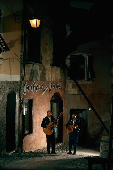 After dark, street musicians play under a streetlight in Portofino, 1965.
