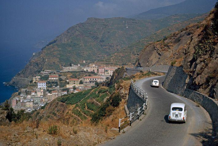 Fiat cars descend a winding hillside road towards the town of Riomaggiore, part of the Cinque Terre ...
