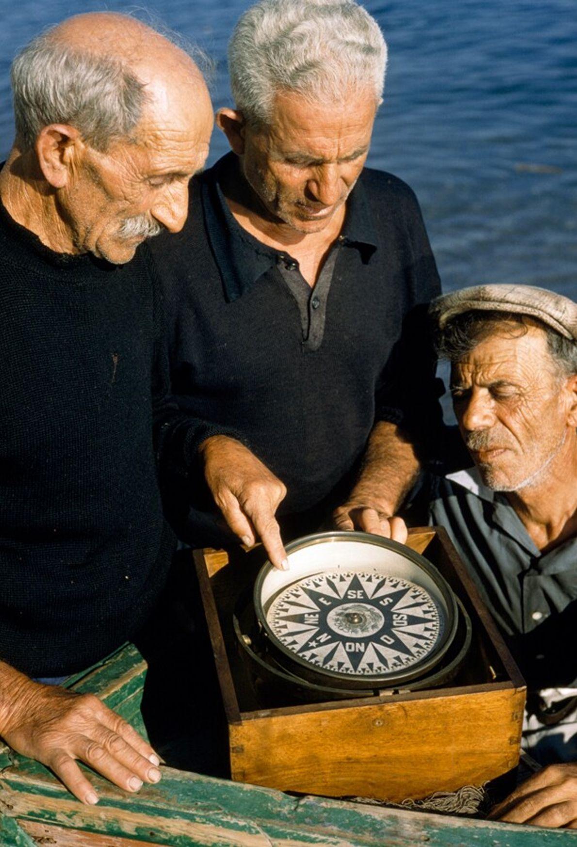 Three fisherman regard an antique mariners' compass off the coast of Amalfi, 1959.