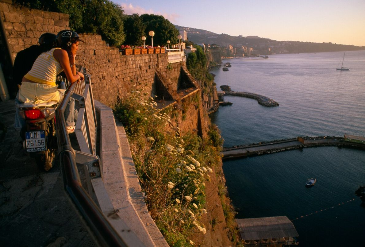 Astride scooters, young people watch the sunset over the bay of Naples near Sorrento. The popularity ...
