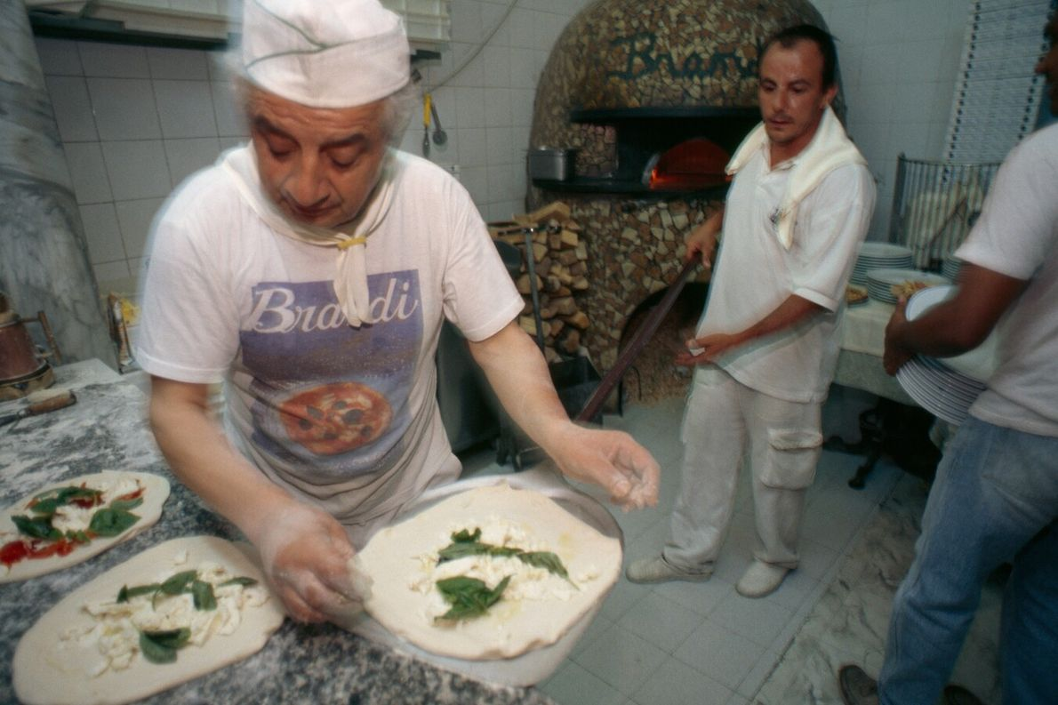 'Pizzaiolo' load pizza into a wood-burning oven, Naples. What most of us now know as pizza ...