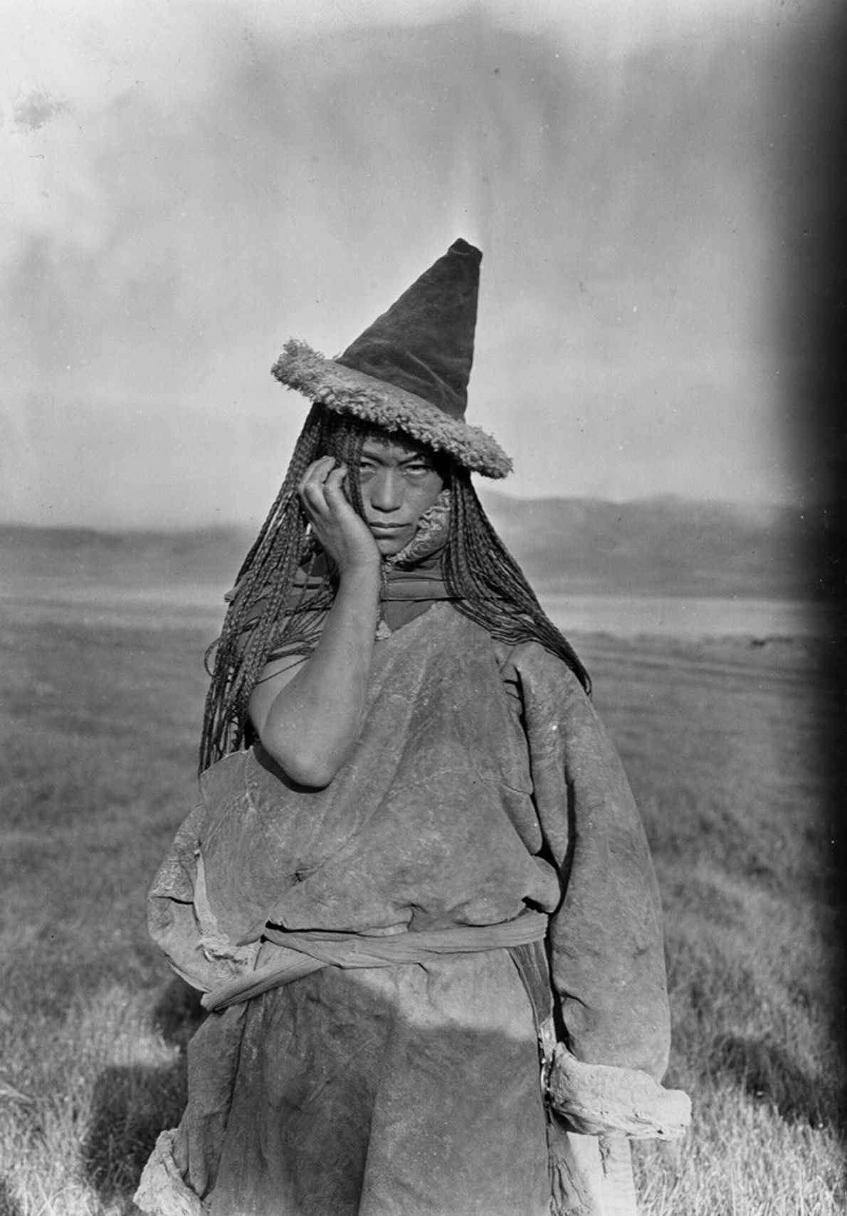China, 1925: a Tibetan nomadic woman wearing a traditional pointed hat poses for the camera. Tibet ...