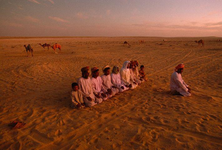 Oman, 1992: Hamad Haraiz Harsousi Bedouins make evening prayer at the Jiddat al Harasis, a desert famous for ...