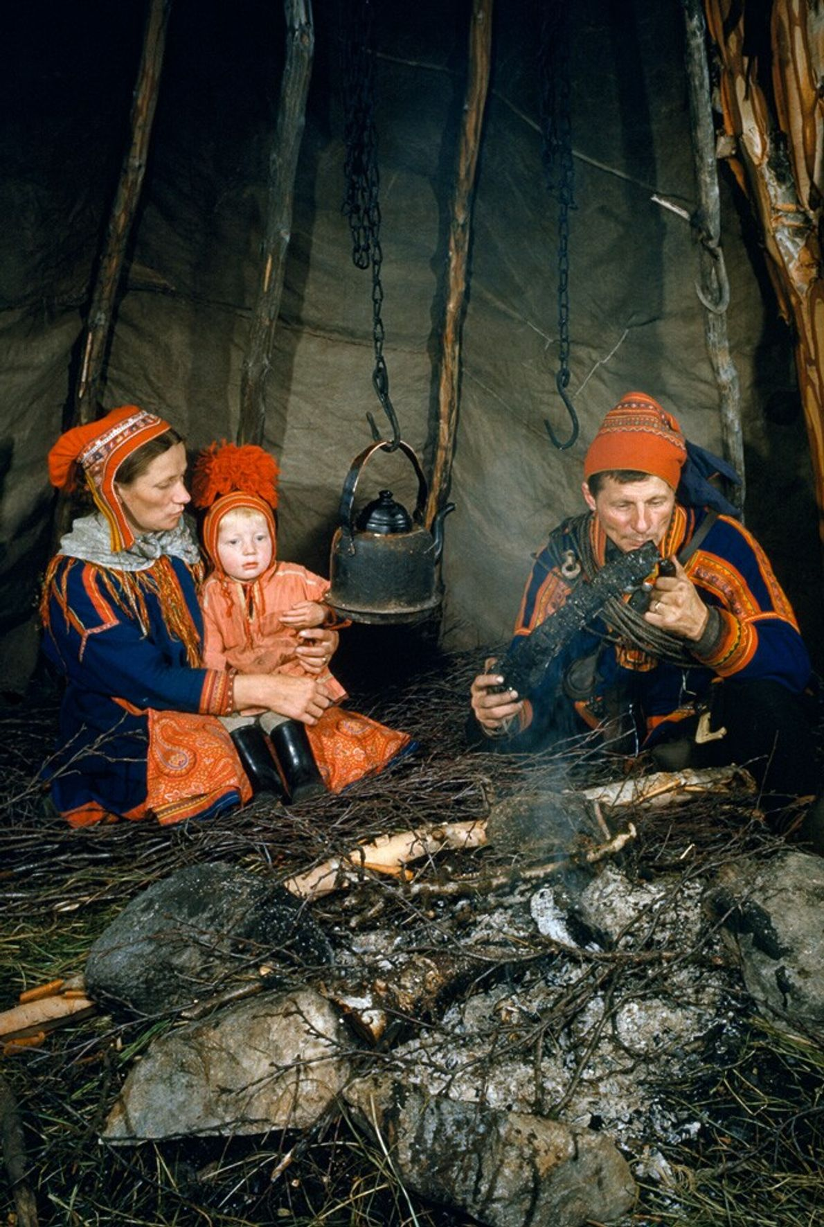 Finland, 1954: a Sami family sit around a fire in a reindeer skin tipi. Also known ...