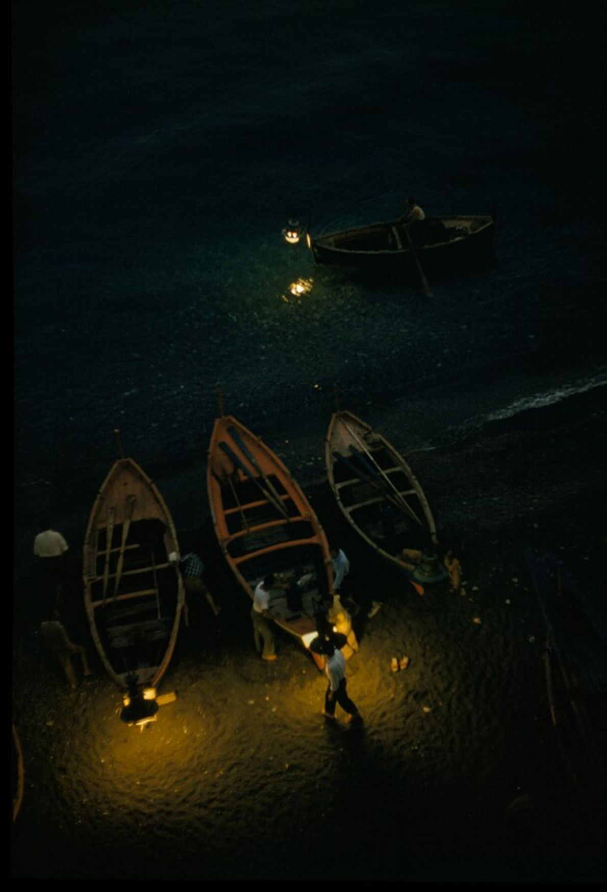 Anchovy fishermen hold lamps by their boats as they cast off at night into the waters ...