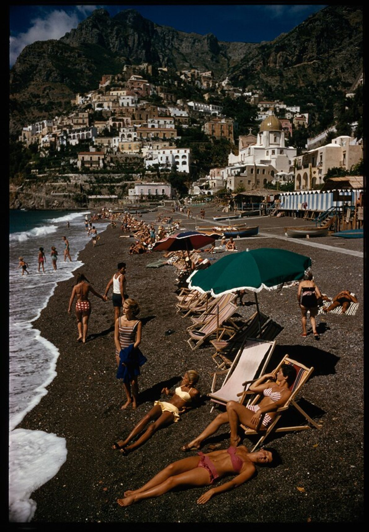 Sunbathers relax beneath the buildings of 'vertical town' Positano, 1959. The glamour of Italy in the ...