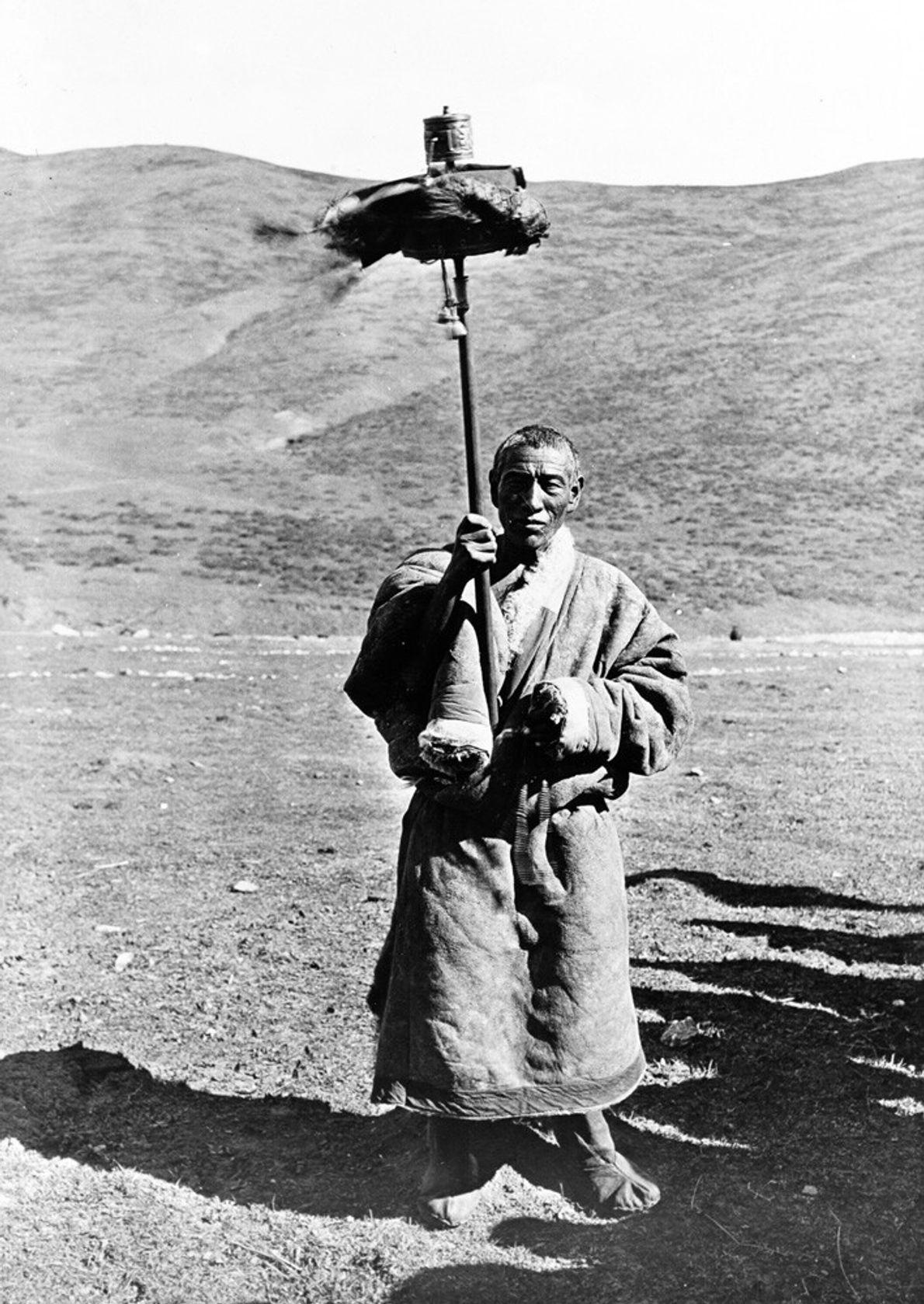 Tibet, 1955: A Tibetan Drokpa nomad twirls a huge prayer wheel along the route between Choni and Xincheng. 'Drokpa' ...