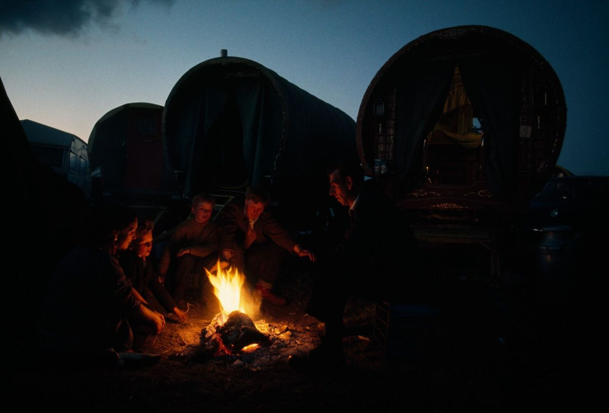 England, 1972: in front of traditional bow top wagons, a family of travellers cook around a camp ...